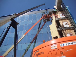 Workers in Aerial Lift Working Outside Building
