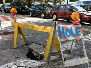 Hole Created in Asphalt on Road, Blocked by Barricade