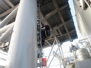 Climber wearing PPE while climbing fixed ladder.