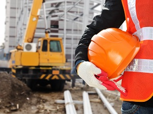 Worker Standing by Crane at Construction Site