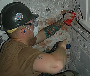Worker using a hammer and chisel to chip away tiles. Notice the proper use of eye protection in the form of safety goggles that include side protectors.