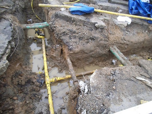 Open excavation showing gas main and other buried utilities.