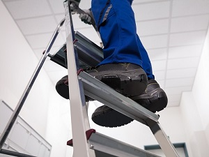 Worker Standing on Step Ladder