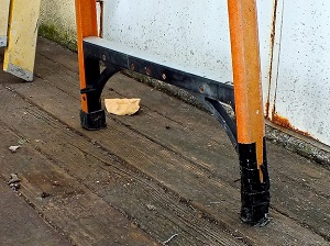 Damaged footpad/assembly on this step ladder was poorly taped over in a bad attempt to fix the ladder.