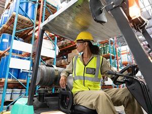 Forklift Operator Backing Up Forklift in Warehouse