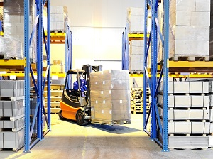Forklift Carrying Load in Aisle of Warehouse