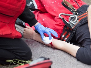 Injured Worker is Bleeding, Laying on Ground, Receiving First Aid