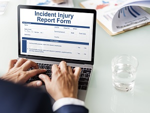 Worker Filling Out Incident Injury Report Form on Laptop