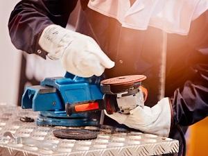 Gloved Worker Replacing Wheel on Grinder
