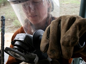 Gloved Worker Wearing Face Shield While Using a Portable Grinder