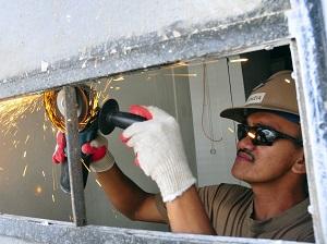 Gloved Worker Grinding Metal