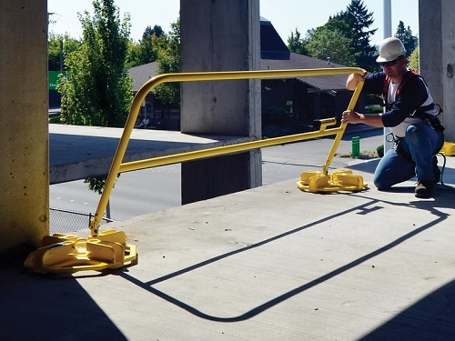 Construction Worker Installing Fall Protection Guardrails