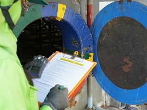 Worker with Confined Space Checklist at Entrance of Confined Space