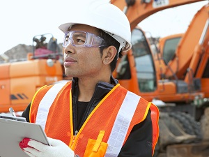 Construction Supervisor with Clipboard, Heavy Equipment in Background