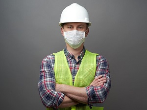 Working Wearing Hardhat, Safety Vest and Face Mask