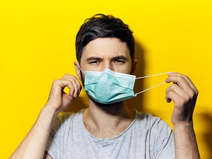 Man Removing Surgical Face Mask by Loops