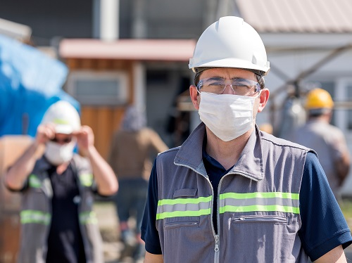 Two Workers with Face Masks Standing Apart