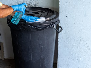 Gloved Hands Disinfecting the Lid of a Trash Can