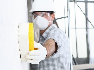 Construction Worker Wearing Face Mask and Gloves is Wiping Wall with Sponge