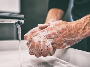 Person Washing Hands with Soap and Water