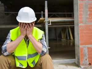 Construction Worker Sitting Down at Construction Site, Feeling Tired