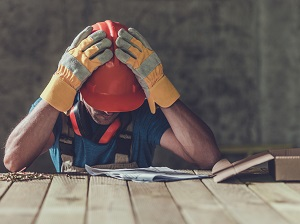 Construction Worker Tired at Work, Head in Hands