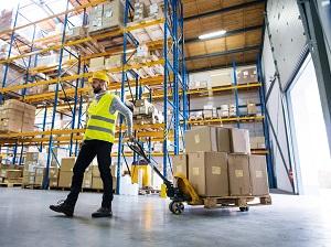 Warehouse Worker Pulling Pallet Jack Near Loading Dock