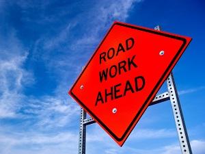 Road Work Ahead Hazard Sign Against Blue Sky