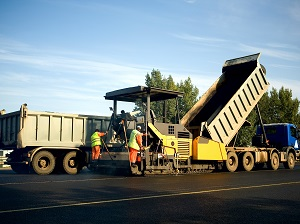 Workers Laying New Asphalt in Work Zone