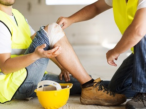 Worker Performing First Aid on Another Worker Who Hurt His Knee