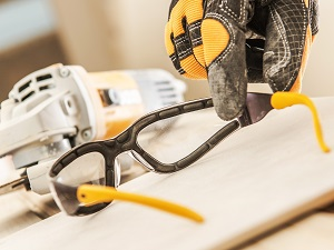 Construction Worker's Hand Reaching for Safety Glasses Before Using Grinder