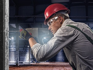 Construction Worker Wearing Safety Glasses While Using Drill