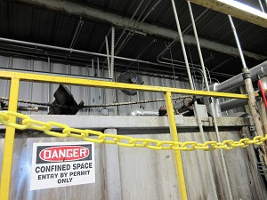 """In a barricaded section of the facility there is a sign that says """"Danger, Confined space entry by permit only."""""""
