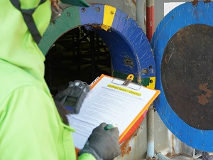 Supervisor reviewing confined space checklist on clipboard before entry