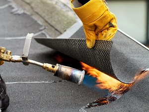 Roofer Using a Torch to Apply Shingles with Tar