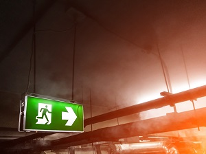 Illuminated Exit Sign Inside Building with Fire and Smoke Visible