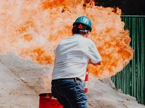 Worker Putting Out Fire with Fire Extinguisher