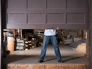Worker Raising Industrial Garage Door to Warehouse