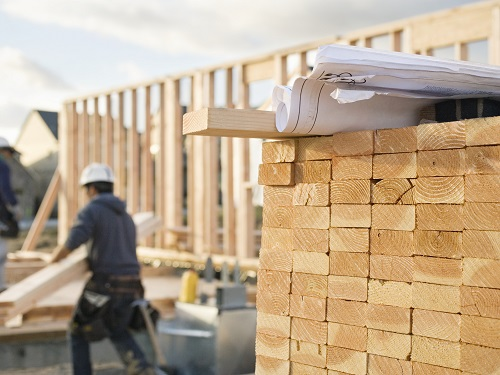 Construction Worker Carrying Lumber on Construction Site