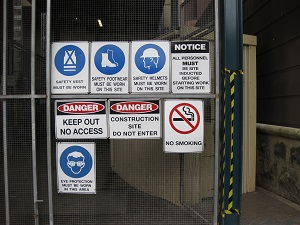 Safety Warning and Danger Signs, Including a No Smoking Sign, Posted on Gate at Entrance of Construction Site