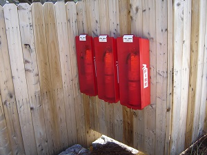Portable Fire Extinguishers Mounted on Wooden Fence