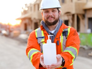 Construction Worker Holding Hand Soap in Front of Construction Site