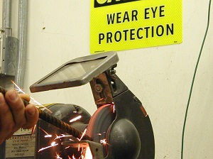 Worker Using Grinder with Caution Sign Above That Says Wear Eye Protection