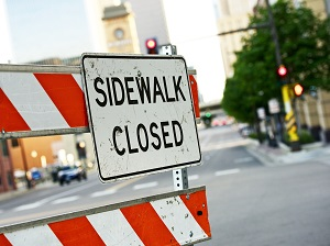 Sidewalk Closed Sign on Warning Barrier