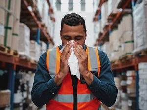 Sick Warehouse Worker Sneezing into a Tissue