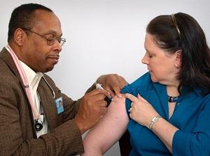 Medical Doctor Providing Flu Shot to Woman