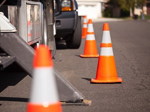Orange Traffic Cones Warning Drivers of Parked Trucks on Roadway