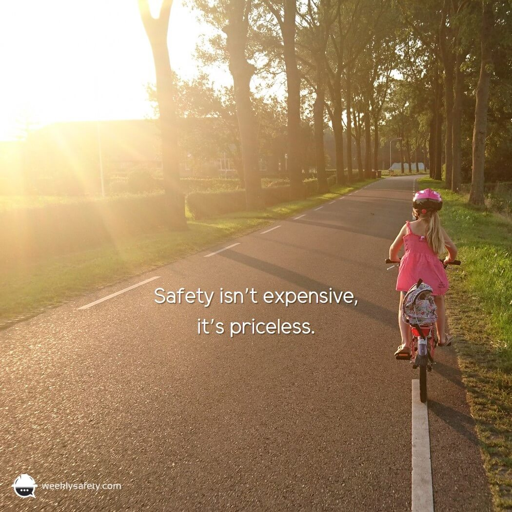 Little girl riding a bicycle on an empty road, wearing bicycle helmet.