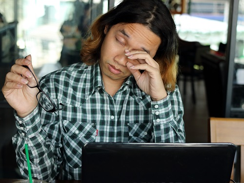 Person Rubbing Eyes After Working on Computer