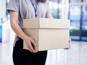 Professional woman holding box, walking through office building.